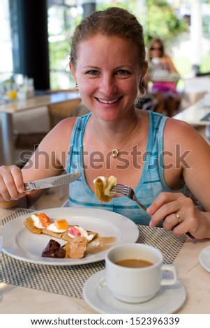 Beautiful lady giving a toothy smile while having crepes along with her coffee - stock photo