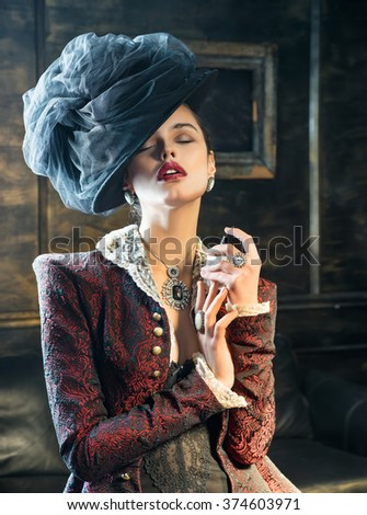 Beautiful lady in a black hat and a red jacket holds a perfume bottle