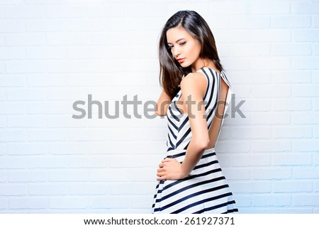 Beautiful lady in black-and-white dress posing near white brick wall. Beauty, fashion concept. - stock photo