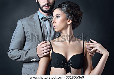 Beautiful lady in bra with handsome guy in suit. Young couple is hugging each other. Portrait of girl in underwear and boy indoors in passionate pose. Beauty woman with attractive lace lingerie - stock photo