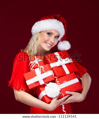 Beautiful lady in Christmas cap hands a set of presents, isolated on purple - stock photo