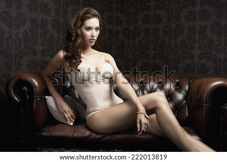 Beautiful lady in lingerie is posing on the posh couch - stock photo