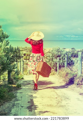 beautiful lady in red traveler in retro style   on the beach - stock photo