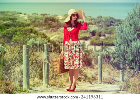 beautiful lady in red traveler  on the beach  in retro style - stock photo
