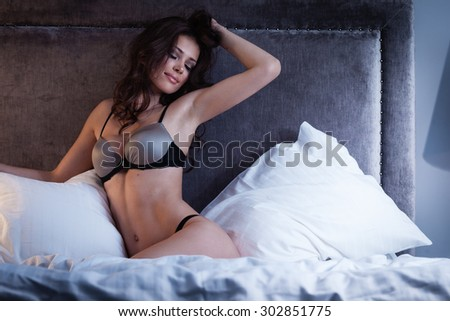 Beautiful lady in sexy lingerie lies in bed - stock photo