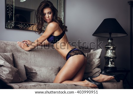 Beautiful lady in sexy lingerie sits on a sofa - stock photo