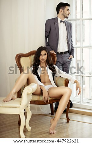 Beautiful lady in shirt with handsome guy in suit. Young couple is hugging each other. Portrait of girl in underwear and boy indoors in passionate pose. Beauty woman with attractive lace lingerie - stock photo