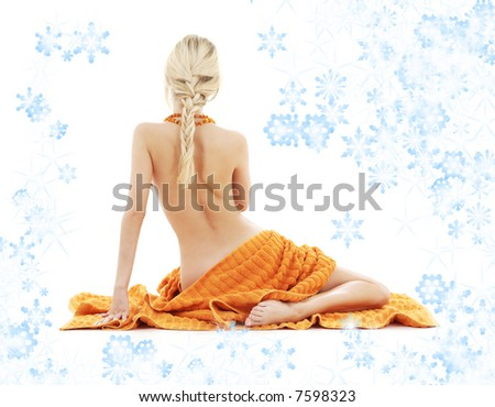 beautiful lady in spa with orange towels and snowflakes - stock photo