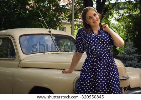 Beautiful lady in vintage dress standing near retro car