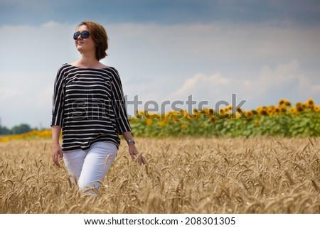 Beautiful lady in wheat field - stock photo