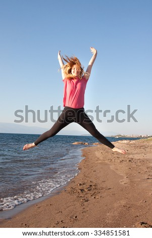 Beautiful lady jumping high on the beach  - stock photo