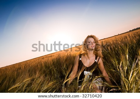 Beautiful lady resting in ripe field of wheat - stock photo