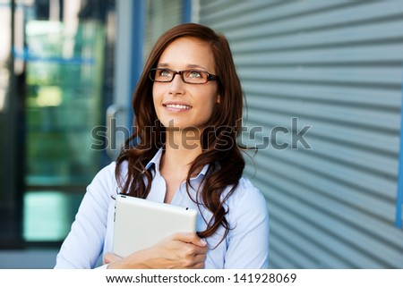 Beautiful lady thinking and holding a tablet - stock photo