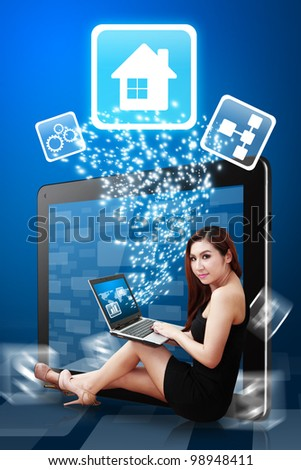 Beautiful lady use notebook computer and present The House icon from Tablet PC - stock photo
