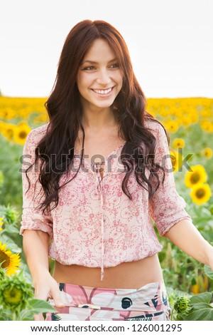 Beautiful lady walking in summer sunflower field - stock photo