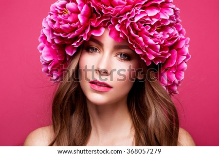 Beautiful lady with a wreath of flowers. Flower style portrait of a young beauty - stock photo