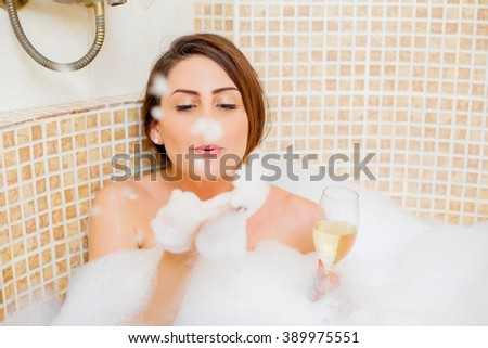 Beautiful lady with champagne playing with foam in the bathtub.