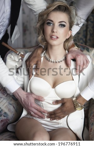 Beautiful lady with cigar and two men's hands - stock photo