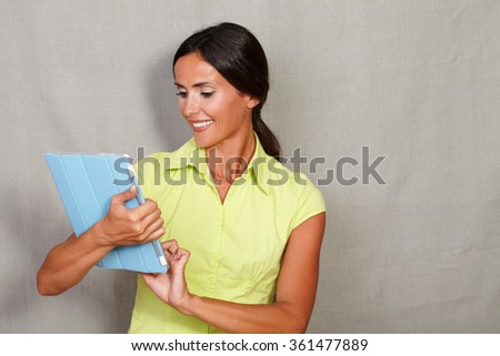 Beautiful lady with long hair and toothy smile holding and using tablet while working in casual clothing against grey texture background