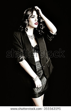Beautiful lady with movie style glam girl fashion look.  Shot on black background.