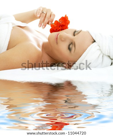 beautiful lady with red flower on white sand - stock photo