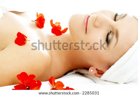 beautiful lady with red flower petals in spa - stock photo