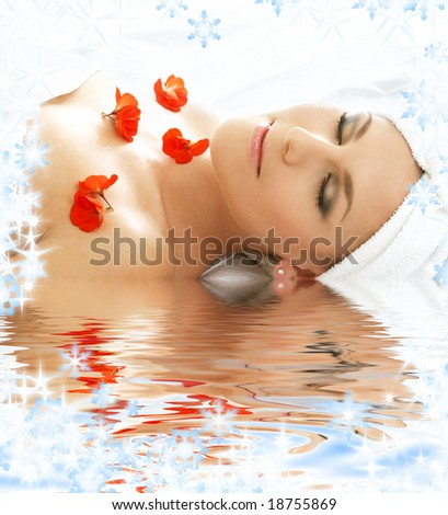 beautiful lady with red flowers in spa - stock photo