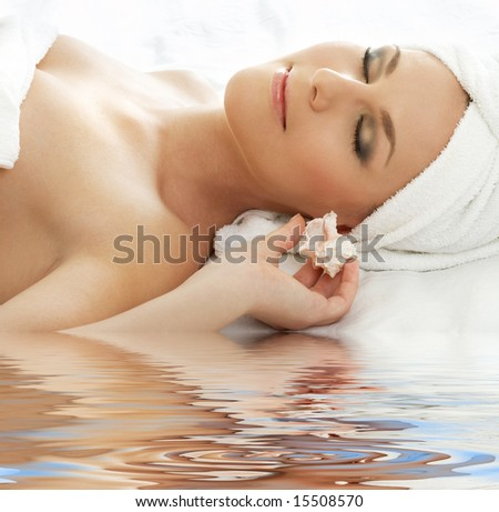 beautiful lady with sea shell in spa - stock photo