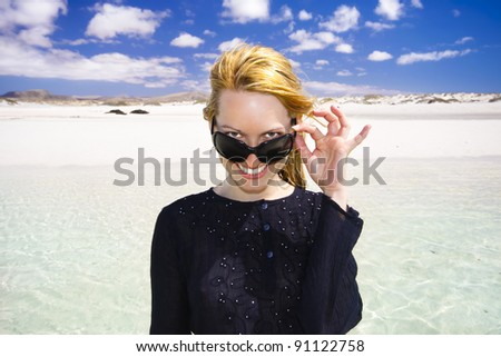 Beautiful lady with sunglasses sending greetings from a tropical vacations with the idyllic scenery in the background. - stock photo