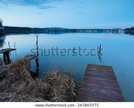 Beautiful lake after sunset with sky reflected in water. Polish lake landscape photographed in Mazury lake district. Place where swans sleeping. - stock photo
