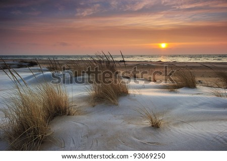Beautiful Lake Huron Sunrise, Tawas Point State Park, Michigan USA Snow and ice mix with the drifting sand making this a pretty winter scene. - stock photo