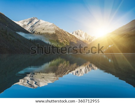 Beautiful lake in Altai mountains. Sunrise and mountains reflected in the water - stock photo