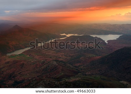 Beautiful lake in the fantastic country Morocco with a kind on the leaving sun. The photo is made with not high mountain. - stock photo
