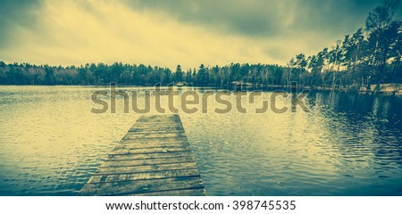 Beautiful lake landscape with romantic wooden pier or wooden jetty over calm water surface, vintage photo - stock photo