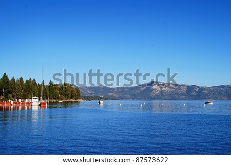 Beautiful Lake Tahoe on a clear blue day surrounded by pines and mountains - stock photo