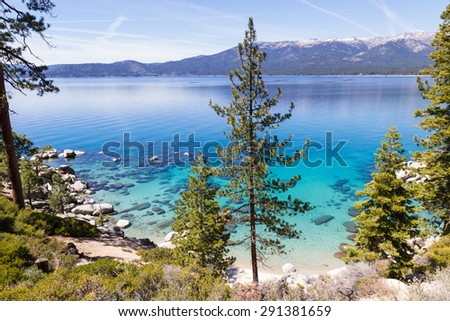 Beautiful Lake Tahoe with chemtrails across the blue sky - stock photo