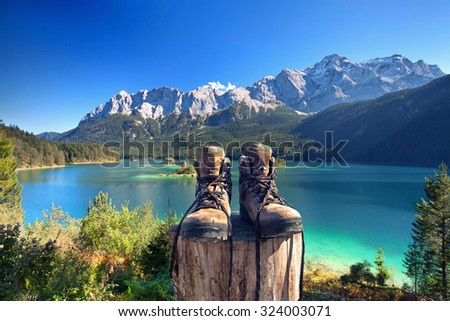 beautiful lake view to eibsee and Zugspitze with hiking boots - stock photo