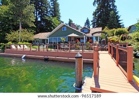 Beautiful lake waterfront property with dock and large deck. - stock photo