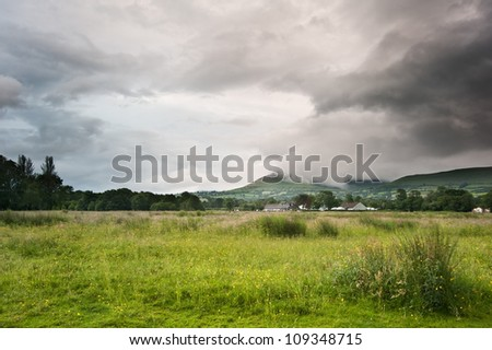 Beautiful landscape across countryside to mountains in distance with moody sky