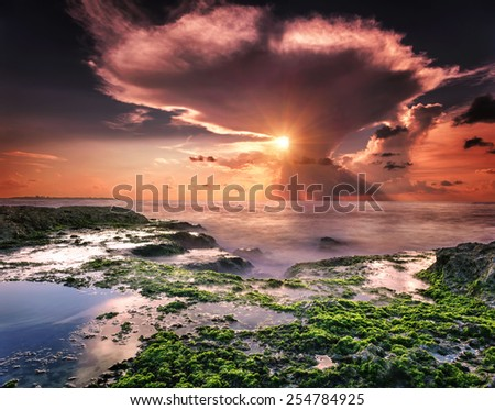Beautiful landscape, amazing bright sunset over sea, gorgeous stony coastline, majestic dramatic cloudscape, beauty of wild nature - stock photo