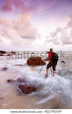 Beautiful landscape at rocky landscape and  old man in the beach in Kemasik Beach, Teranggan,  on a long exposure. Soft Focus due to Long Exposure Shot - stock photo