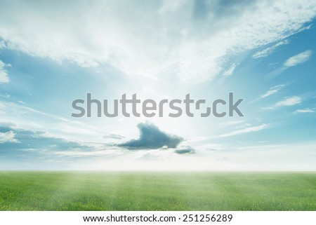 Beautiful landscape. Clouds with sunbeams on blue sky at summer sunny day over the green meadow - stock photo