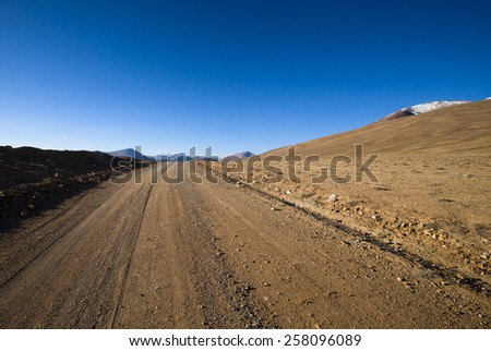Beautiful landscape - country road in desert valley. The rocky mountains and blue sky are behind. Toned. - stock photo