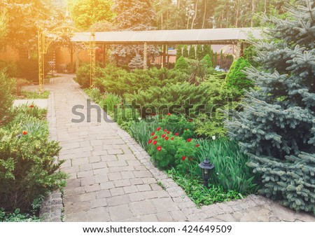 Beautiful landscape design, garden path with stone tiles, evergreen bushes, fir trees, blue spruces and shrubs in sunlight. Modern landscaping. Summer garden or park design. - stock photo
