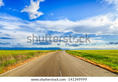 Beautiful landscape field of wheat, road, clouds and mountains. HDR image - stock photo