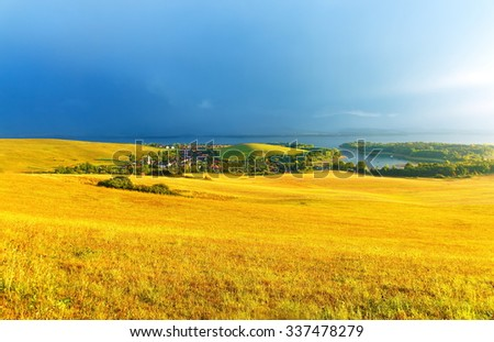 Beautiful landscape, green and yellow meadow and lake with mountain in background. Slovakia, Central Europe