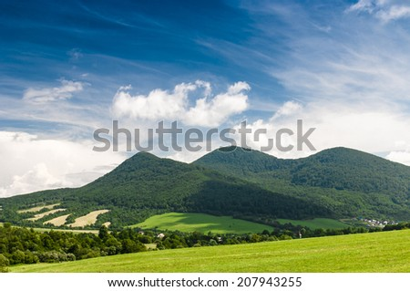 Beautiful landscape. Green hills and blue sky with white clouds - stock photo