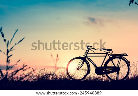 beautiful landscape image with Silhouette  Bicycle at sunset in vintage tone style - stock photo
