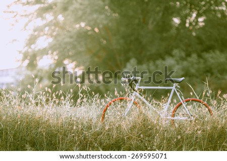 beautiful landscape image with white Bicycle at sunset