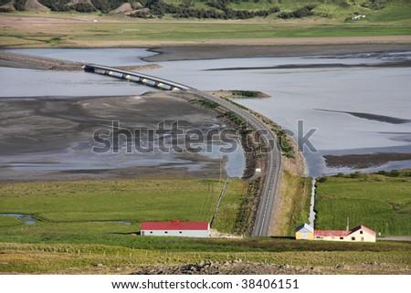 Beautiful landscape in Iceland. Lagarfljot lake bridge and farm buildings. - stock photo